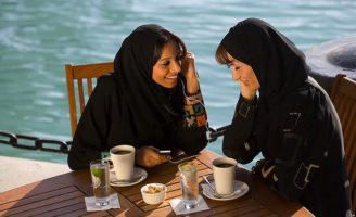 Women Listening to an MP3 Player Over Coffee in Dubai, UAE © Peter Adams/Corbis