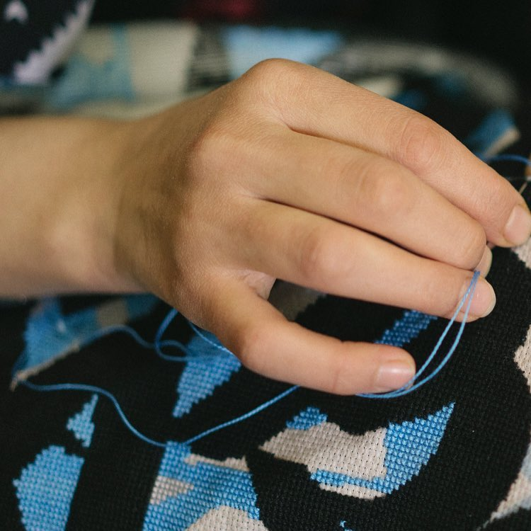 """a social enterprise that promotes the tradition of """"tatreez"""", a cross-stitch embroidery art, while improving the daily lives of its female refugee employees"""