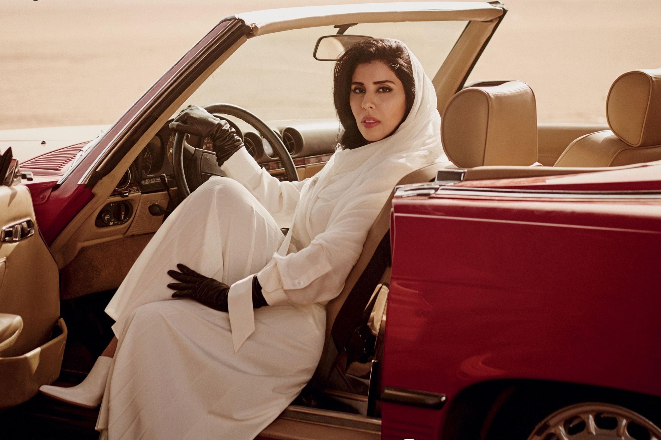 La princesse Hayfa pose aux commandes d'une décapotable rouge. en Une de Vogue Arabia © Vogue Arabia